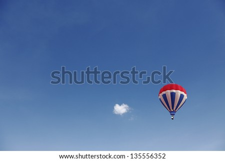 A colorful exotic hot air balloon floating in a serene blue sky with a small cloud. - stock photo
