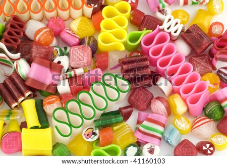 A colorful full frame holiday candy background, vivid colors with ribbon candy, peppermint, and an assortment of Christmas hard candies - stock photo