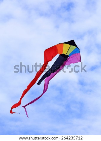 A colorful kite flies in a partly cloudy sky.