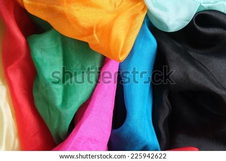 A colorful mixture of several shiny silk handkerchiefs. Red, blue, aqua blue, black, yellow, orange, pink, fuchsia, golden, green - stock photo