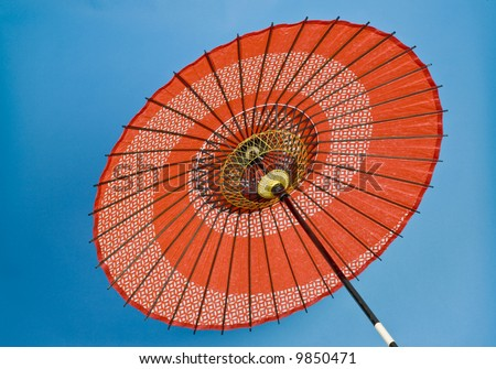 A colorful oriental umbrella, red on a blue background.