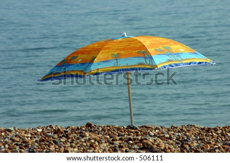 A colorful parasol on the beach - stock photo