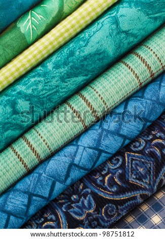 A Colorful Stack of Cloth Fabrics Set at a Diagonal Angle in Soothing Blue and Green Tones and may be Used  in a Quilt - stock photo