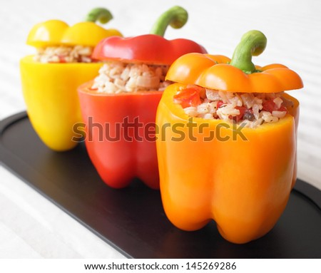 A colorful trio of bell peppers stuffed with rice, mushrooms, and tomatoes. - stock photo