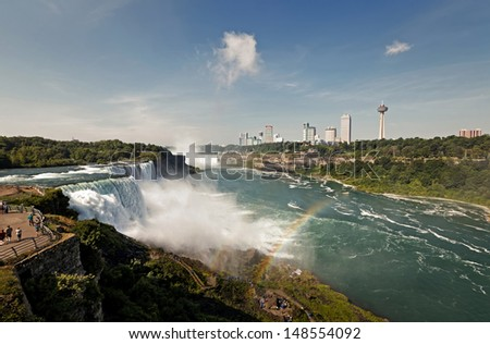 A colorful view of the Niagara Falls and rainbow at sunrise - stock photo