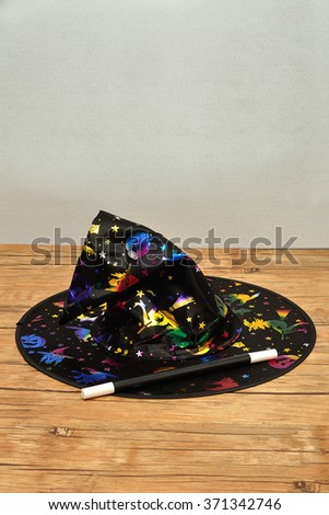 A colorful witches hat with a magic wand - stock photo