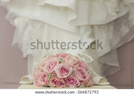 A coloured macro photo of a detailed bouquet with pink roses, white small flowers and a fake diamond in the centre of the roses, the wedding dress and shoes