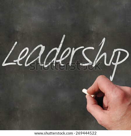 A Colourful 3d Rendered Concept Illustration showing a hand writting Leadership on a blank blackboard - stock photo