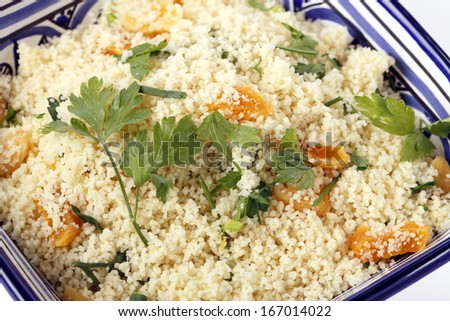 A colourful Tunisian blue and white bowl with couscous mixed with chopped dried apricots and fresh parsley - stock photo