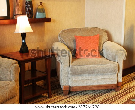 A comfy armchair with orange pillow near a small table - stock photo