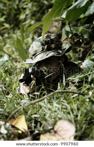 A commando aiming his rifle in the bushes - stock photo