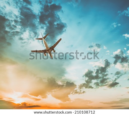 A commercial jet taking off into the sunset - stock photo