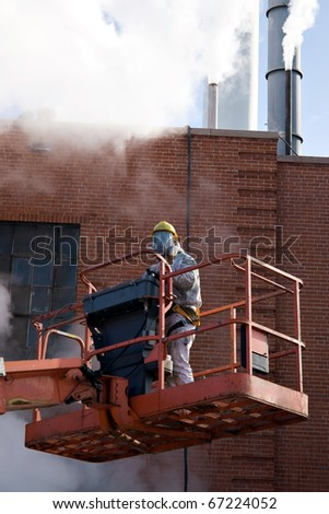 A commercial painter suited up with an industrial painting mask and suit white standing on a mechanical lift. - stock photo