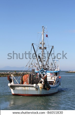 A commercial seine boat leaves Steveston Harbor for the fishing grounds. Near Vancouver, British Columbia. - stock photo