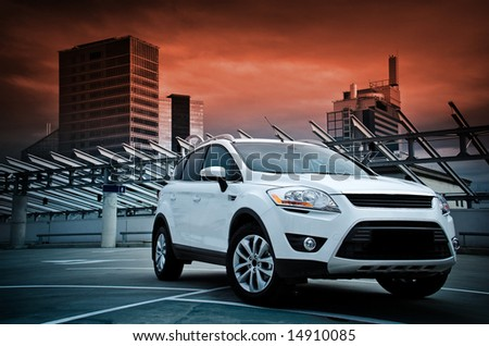 A compact SUV in the city. Dramatic sky. - stock photo