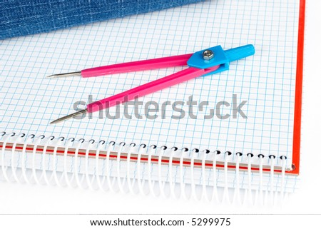 A compass and blue pencil case over a notebook - stock photo