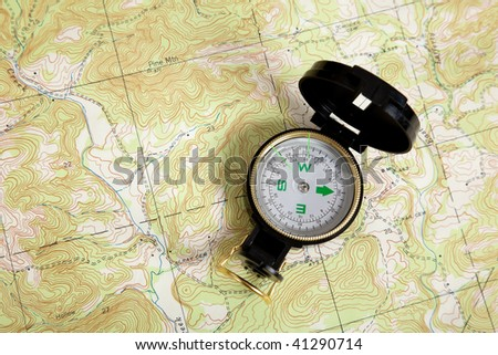 A compass on a topographical map - stock photo