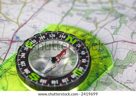 A compass with marked degrees and a north heading on a paper map - stock photo