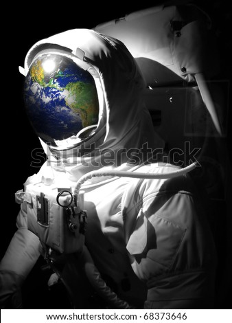 A complete astronaut space suit with a reflection of the earth reflecting in the helmet.  Selective color.  Earth photo courtesy of NASA. - stock photo