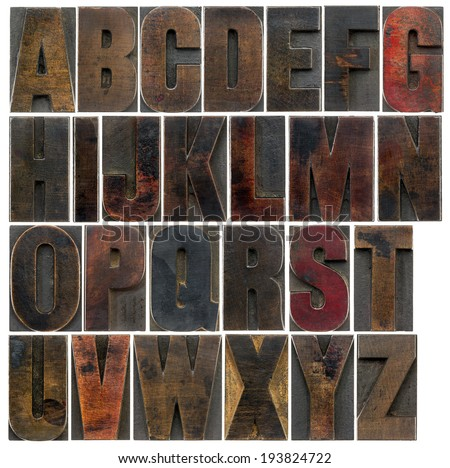 a complete English uppercase alphabet - a collage of 26 isolated antique wood letterpress printing blocks, stained by dark color inks - stock photo
