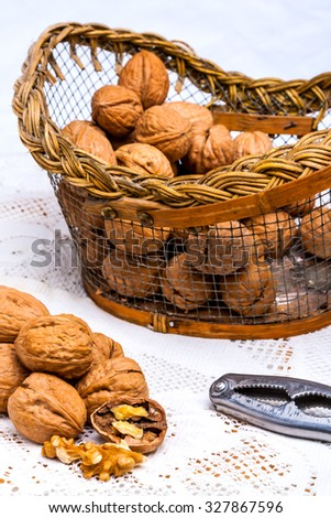 A composition of walnuts, cracked walnuts and a nutcraker - stock photo