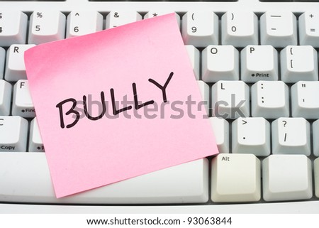 A computer keyboard with a sticky note saying bully, Internet bullying - stock photo
