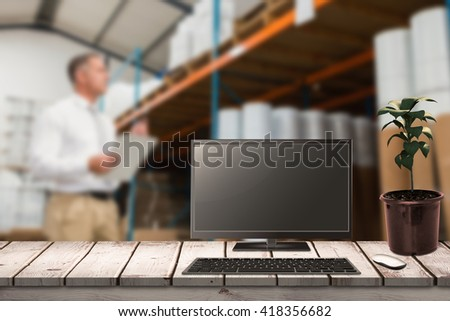 A computer over a desk against warehouse manager checking his list on clipboard - stock photo