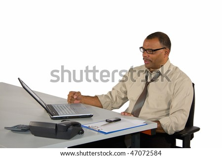 a concentrated mature African-American businessman in a shirt sitting in front of his laptop and receiving good news, isolated on white background - stock photo