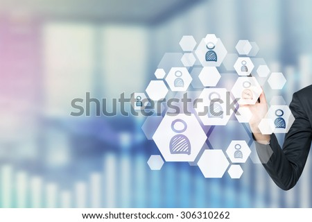 A concept of recruitment process. A hand is choosing the right icon as a concept of the right candidate. Office view in blur. - stock photo