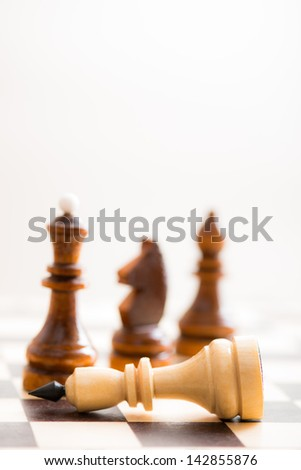 A conceptual composition of chess pieces standing over defeated king on chessboard