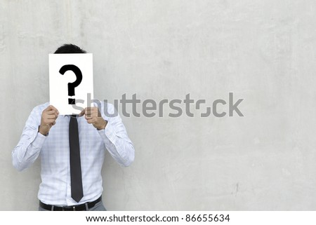 A conceptual image about choice. The Asian man is holding a Question mark sign - stock photo