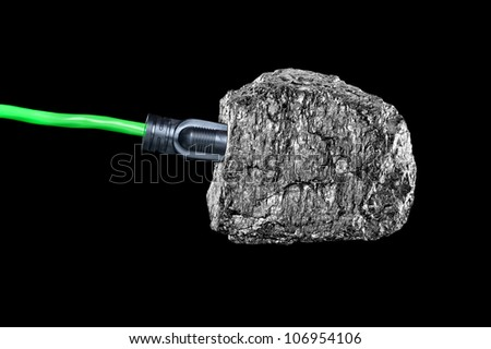 A conceptual image of an extension cord plugged into a chunk of bituminous coal isolated on black. - stock photo