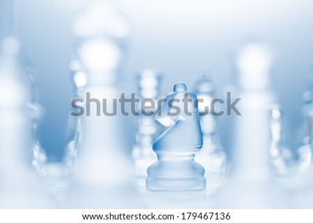 A conceptual photo of a transparent knight on a chessboard making an l-shaped move. - stock photo