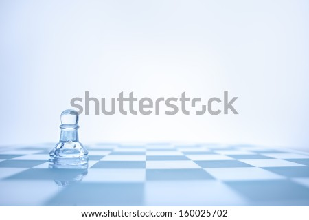 A conceptual photo of loenely glass pawn on the chessboard. - stock photo