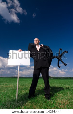 A conceptual picture business executive standing in the countryside with his chair and a signpost, depicting that he is without an office  Available space for text.