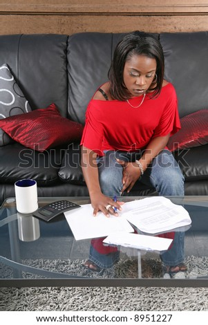 a concerned woman reading a bill or a letter with a pen and a calculator