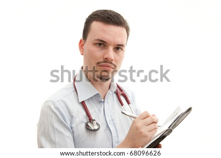A concerned young caucasian male doctor writes notes - stock photo