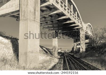 A concrete bridge over railroad tracks in a sunny winter day - stock photo