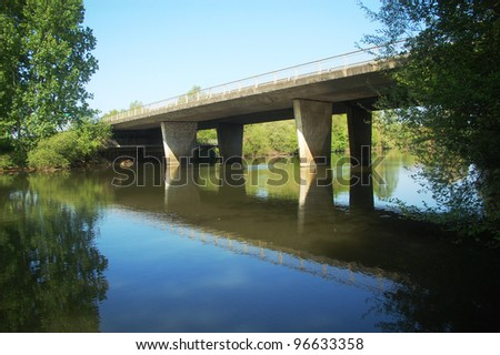 A concrete bridge passing over the river Sarthe in France.