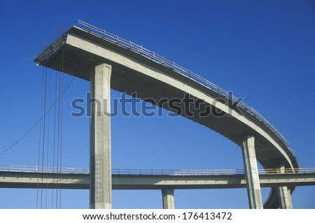A concrete freeway structure ends abruptly with iron support structures sticking out and safety rails lining the top edge until further construction is continued, USA - stock photo