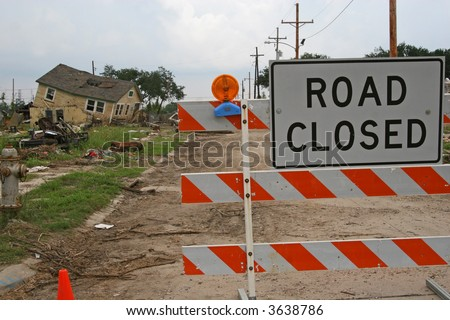 "A condemned home and other debris in the 9th Ward of New Orleans, Louisiana, damaged in Hurricane Katrina. A ""Road Closed"" sign keeps people out. - stock photo"