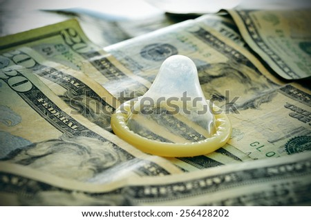a condom on a pile of dollar banknotes, depicting the idea of paying for sex, the sex commerce, the sex industry or the contraceptives industry - stock photo