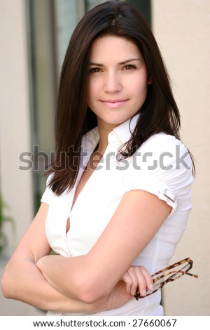 A confident business woman smiles toward camera - stock photo
