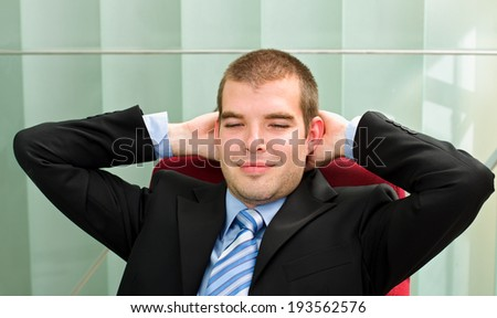 A confident businessman resting in his office - stock photo