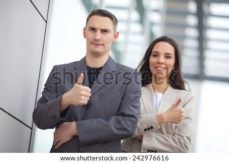 A confident businessman with his female colleague in the background. - stock photo