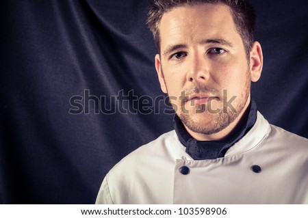 A confident cook against dark background