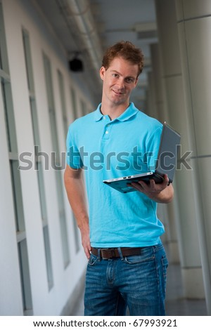 A confident head cocked college guy holds a laptop in a beautiful campus hallway.  Tall handsome male caucasian English model wearing blue shirt looking at camera