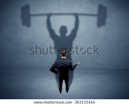 A confident young elegant salesman with briefcase facing a wall, looking at his strong, weight lifting shadow concept - stock photo