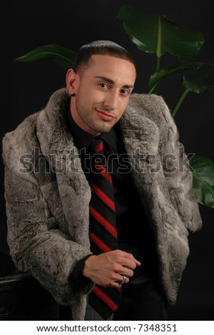 A confident young man in a fur coat at a nightclub