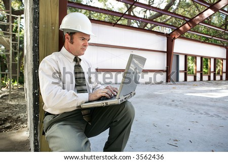 A construction engineer or inspector on the construction site with his laptop. - stock photo
